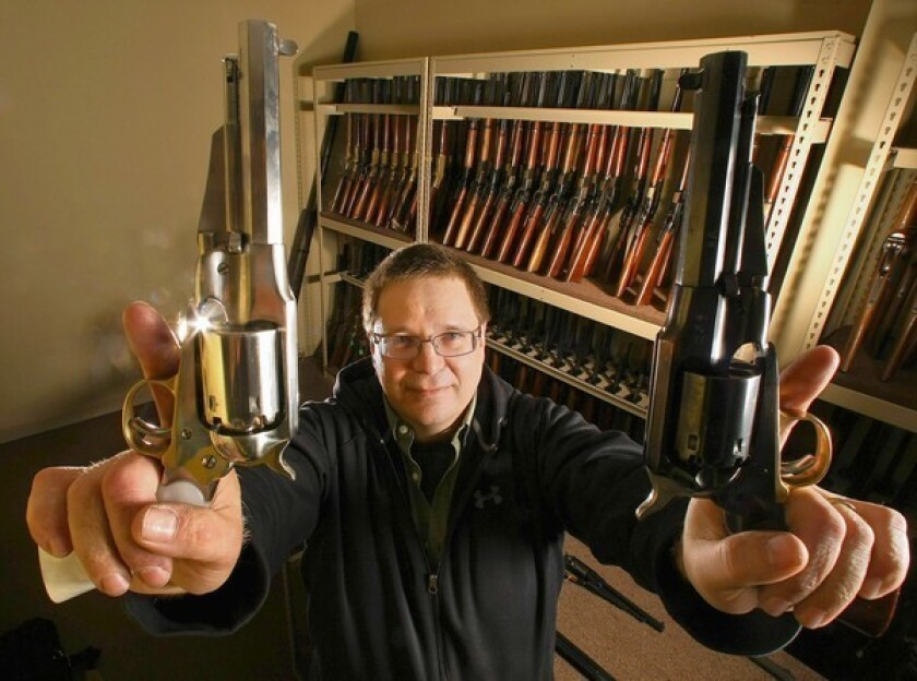 """Larry Zanoff, an armorer who worked on the movie """"Django Unchained,"""" holds up 1858 Remington revolvers that were used in the movie. Zanoff was photographed inside the western room at Independent Studio Services in Sunland."""