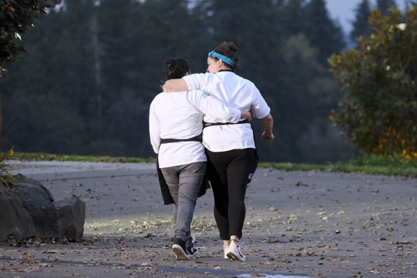 Two women in chef's coats walk away from the camera, arms around each other.
