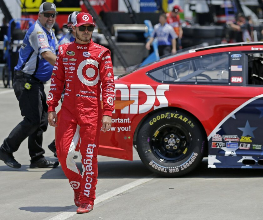 aKyle Larson walks through the garage before practice for Sunday's NASCAR Sprint Cup series auto race at Charlotte Motor Speedway in Concord, N.C., Thursday, May 26, 2016. (AP Photo/Chuck Burton)