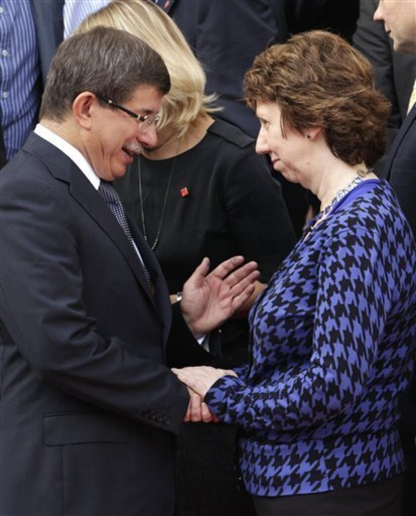 EU High Representative for Foreign Affairs Catherine Ashton, right, talks with Turkey's Foreign Minister Ahmet Davutoglu as they pose for a group photo during a meeting of EU foreign ministers and candidate countries, at the Egmont Palace in Brussels on Saturday, Sept. 11, 2010. (AP Photo/Yves Logghe)