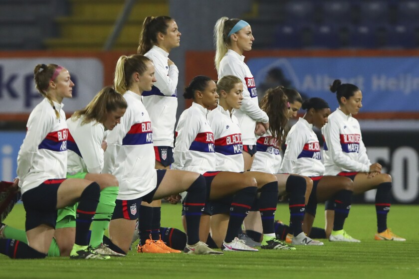 """U.S. players, most kneeling, wear warmups with the words """"Black Lives Matter"""" during the national anthem"""