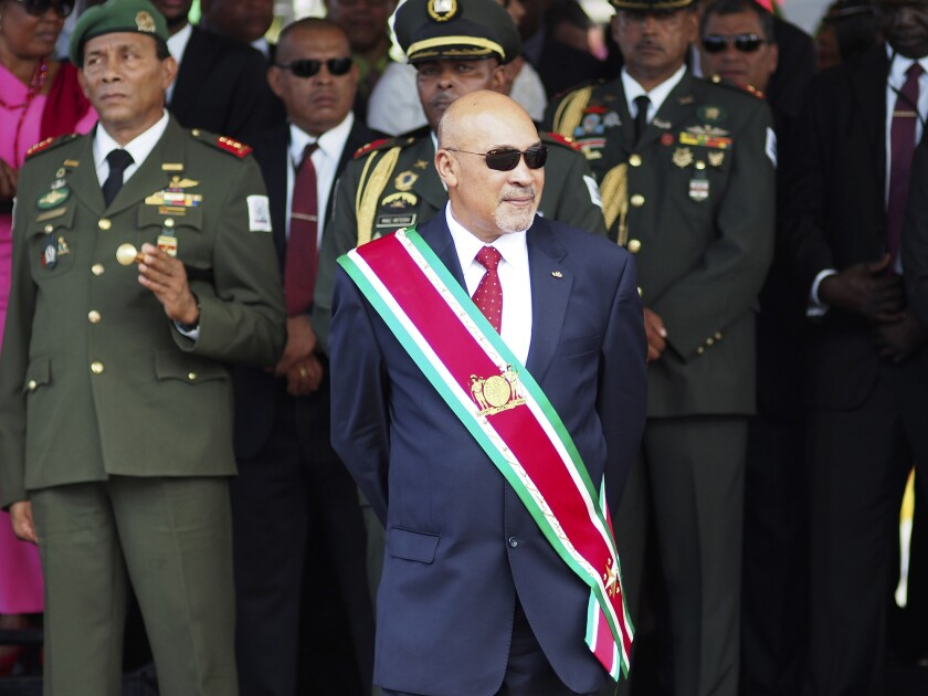 "FILE - In this Aug. 12, 2015 file photo, Suriname President Desire ""Desi"" Delano Bouterse observes a military parade, after being sworn in for his second term, in Paramaribo, Suriname. A Suriname court on Friday, Nov. 29, 2019, convicted Bouterse in the 1982 killings of 15 political opponents and sentenced him to 20 years in prison. (AP Photo/Ertugrul Kilic, File)"