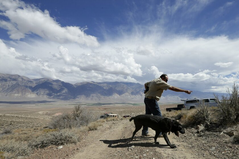 In this Sept. 20, 2014, photo, Paul Dotsie points as his dog Buster sets off to search an area near Bishop, Calif. For years, Buster and Dostie have worked together to unlock mysteries, to find the bodies of fighting men who fell long ago on foreign battlefields, or of victims of unsolved crimes or