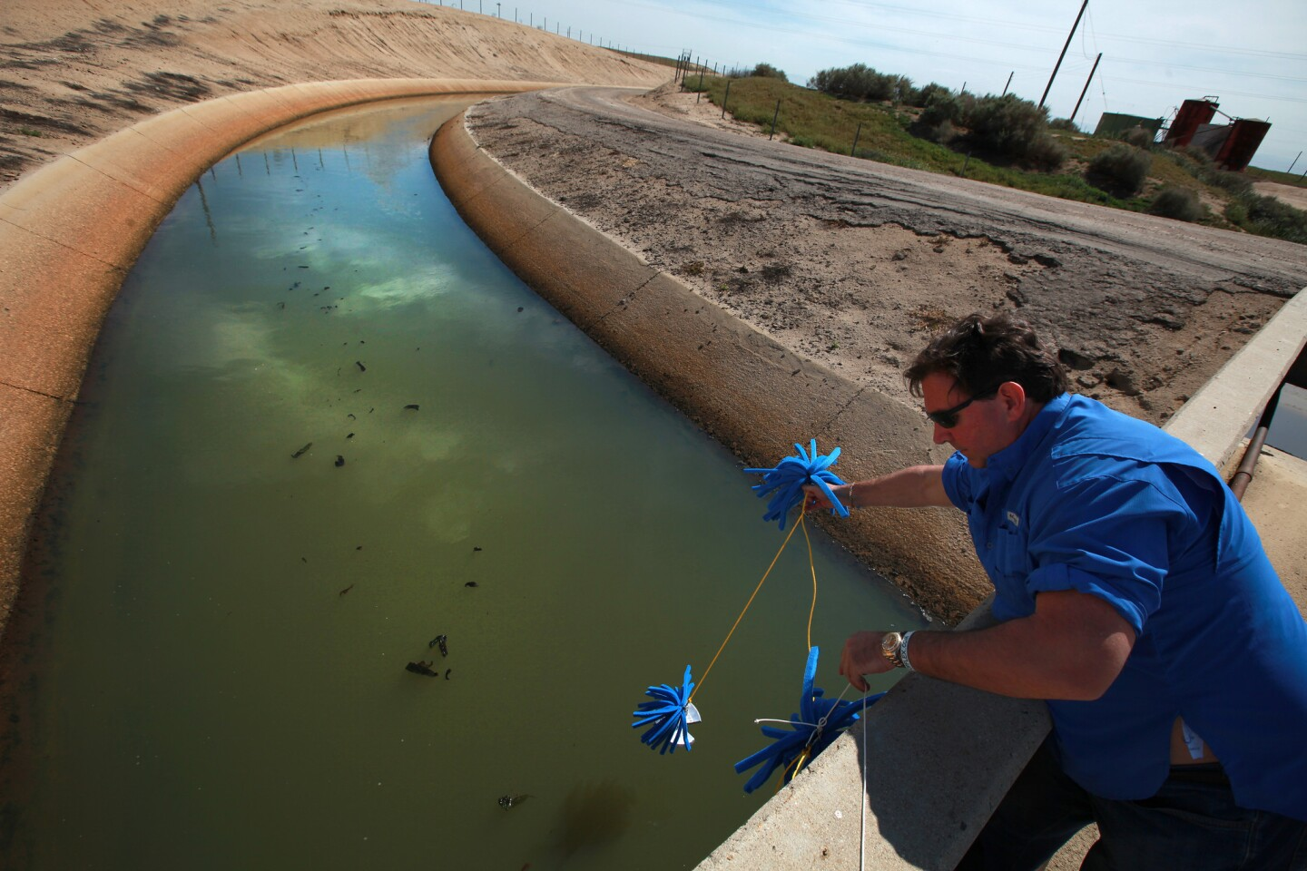 Scott Smith, chief scientist at Water Defense, deploys foam sponges to absorb test water from a canal operated by the Cawelo Water District near Bakersfield. The canal moves oil-produced water mixed with fresh water for use by Kern County farms.