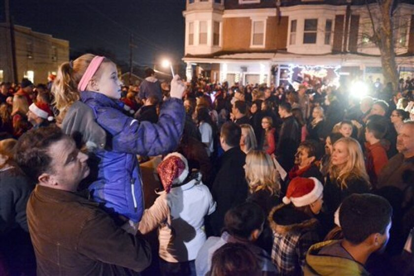 """In West Reading, Pa., thousands of people gathered on Saturday to sing Christmas carols at the home of Delaney """"Laney"""" Brown, 8. Mike Simmons holds his daughter Gracie, 11, while Gracie shoots video of the event. The Brown family announced Laney's death on Christmas Day."""