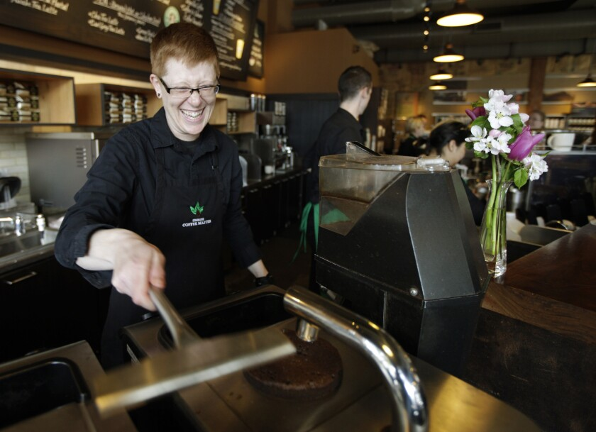 Barista Linsey Pringle prepares a cup of coffee at a Starbucks store in Seattle in 2012. Starbucks said Monday it would reimburse employees who pursue a college degree online.