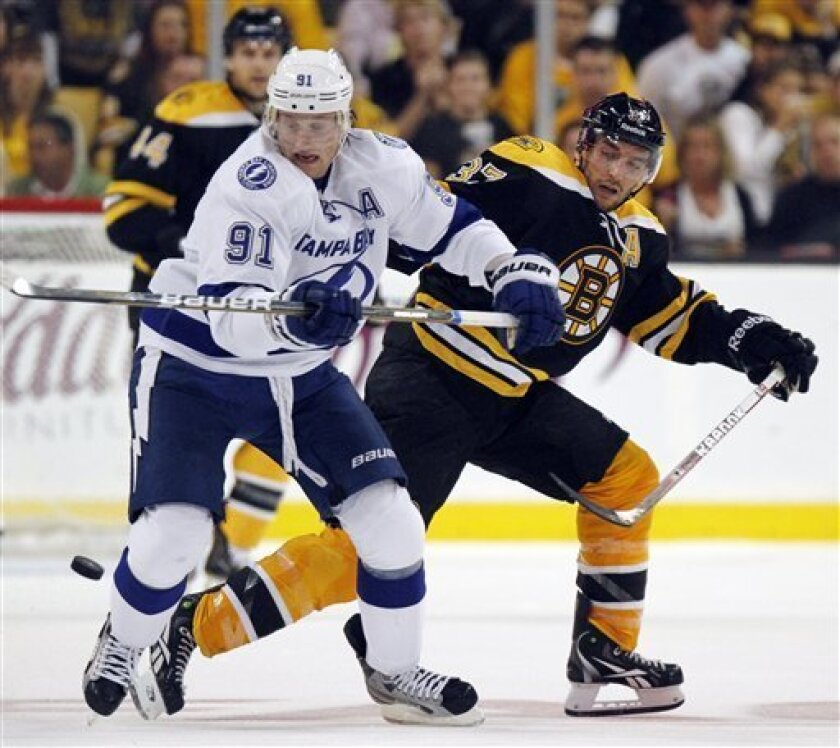 Tampa Bay Lightning's Steven Stamkos (91) battles Boston Bruins' Patrice Bergeron (37) for the puck in the second period of an NHL hockey game in Boston, Saturday, Oct. 8, 2011. (AP Photo/Michael Dwyer)