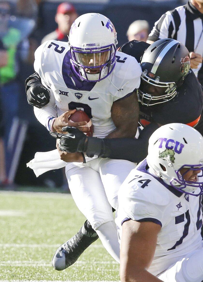 TCU quarterback Trevone Boykin (2) is sacked by Oklahoma State defensive end Jarrell Owens in the second quarter of an NCAA college football game in Stillwater, Okla., Saturday, Nov. 7, 2015. (AP Photo/Sue Ogrocki)
