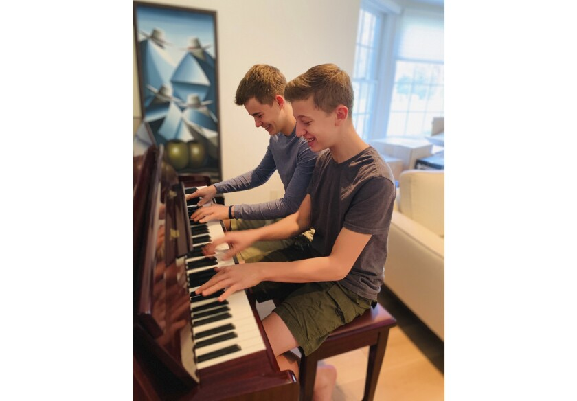 This Nov. 20, 2020 photo released by Andrea Fage shows brothers Rafael Fage, 16, background, ad Noah Fage, 14 playing the piano at their home in Harrison, N.Y. During the pandemic lockdown, private piano lessons for boys stopped. They researched movie soundtracks and learned the score on their own with the assistance of sites like YouTube. (Andrea Fage via AP)