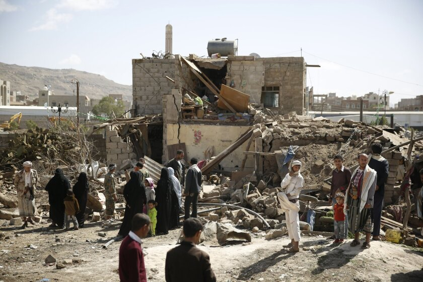 People gather at the site of a house destroyed by a Saudi-led airstrike in Sanaa, Yemen, Thursday, Feb. 25, 2016. (AP Photo/Hani Mohammed)