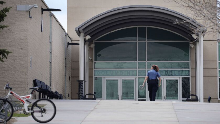A police officer walks to the front doors of Columbine High School, Wednesday, April 17, 2019, in Li