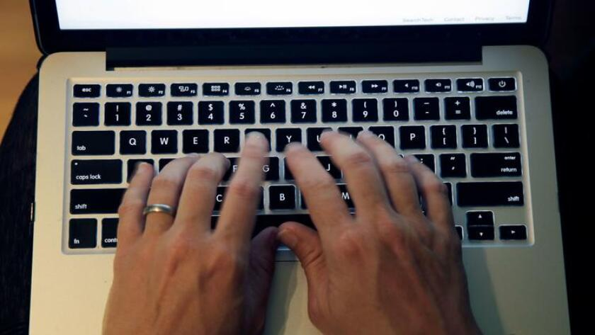 Typing on a laptop.
