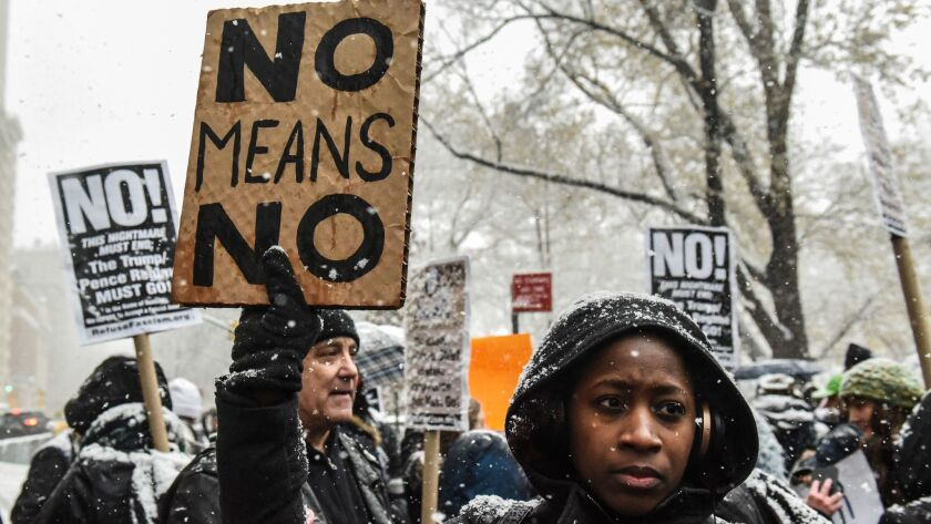People carry signs at a New York protest against sexual harassment on Dec. 9.