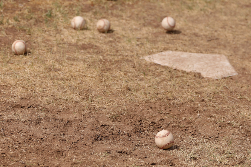 Baseballs are seen on the dirt around a home plate.