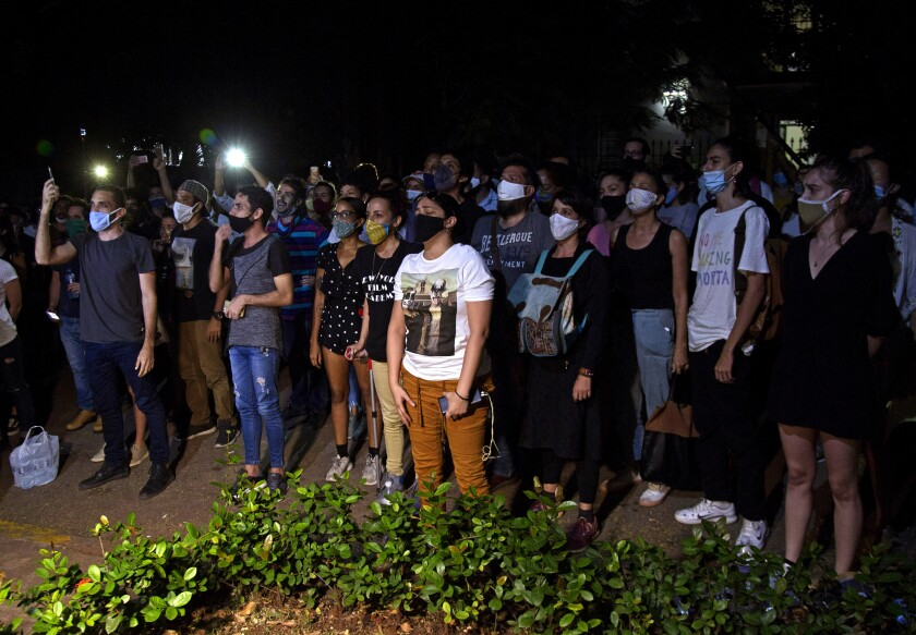 Masked protesters stand together in Havana