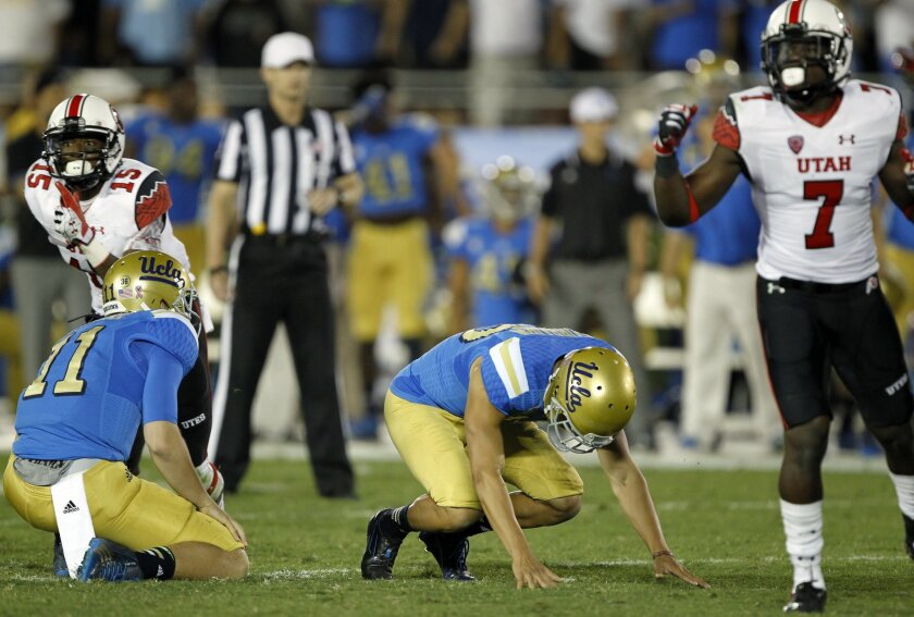 UCLA place kicker Ka'imi Fairbairn, center, falls on his hands after missing a 50-yard field goal with no time remaining, as Utah's Dominique Hatfield (15) and Andre Godfrey (7) celebrate defeating UCLA 30-28 in an NCAA college football game Saturday, Oct. 4, 2014, in Pasadena, Calif. (AP Photo/Alex Gallardo)
