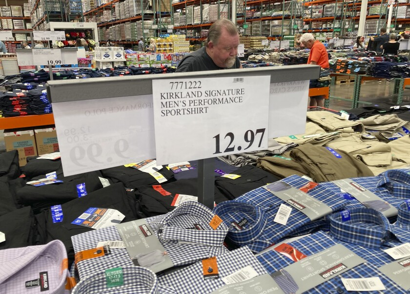 A sign displays the price for shirts as a shopper peruses the offerings at a Costco warehouse on Thursday, June 17, 2021.