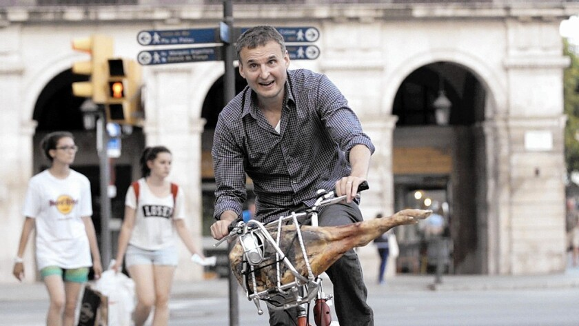 """In an episode of the new series """"I'll Have What Phil's Having,"""" Phil Rosenthal rides around Barcelona with a jamón in his bicycle basket. The show will air locally on KOCE-TV."""