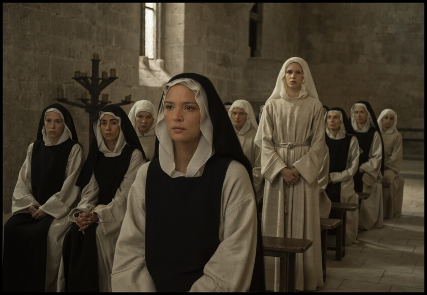 Nuns sit and stand in a room.
