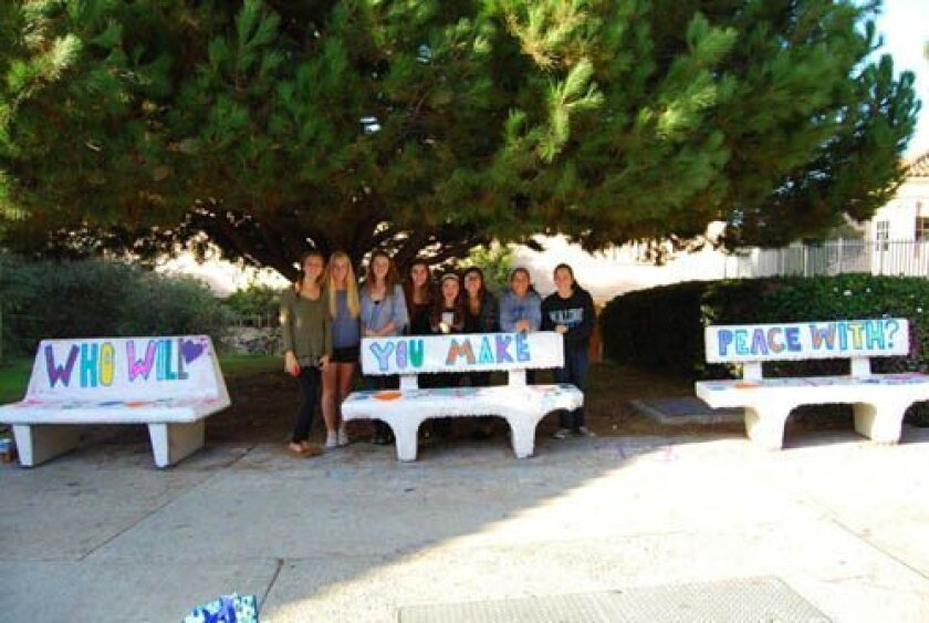 Summer Broekema, Sophia Bourne, Madeleine Garay, Talia Chalhoub, Caroline Garay, Sophia Albaisa, Julia Albanez and Andrea Albanez with their three-part message of benches they painted at La Jolla High School as a project of the Kindness Counts club.