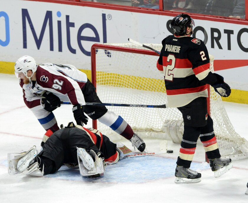 Colorado Avalanche's Gabriel Landeskog celebrates as he steps over Ottawa Senators goalie Andrew Hammond and new teammate Dion Phaneuf as they react to a goal during first period NHL hockey action in Ottawa, Canada, Thursday, Feb. 11, 2016. (Sean Kilpatrick/The Canadian Press via AP) MANDATORY CRED