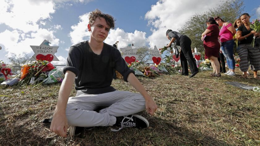 Chris Grady, a student at Marjory Stoneman Douglas High School, sits at a memorial in Parkland, Fla., a few days after the Feb. 14 school shooting.