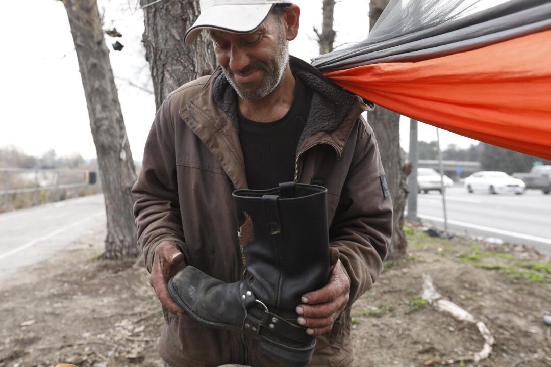 Tyrone Hart holds Harley-Davidson boots