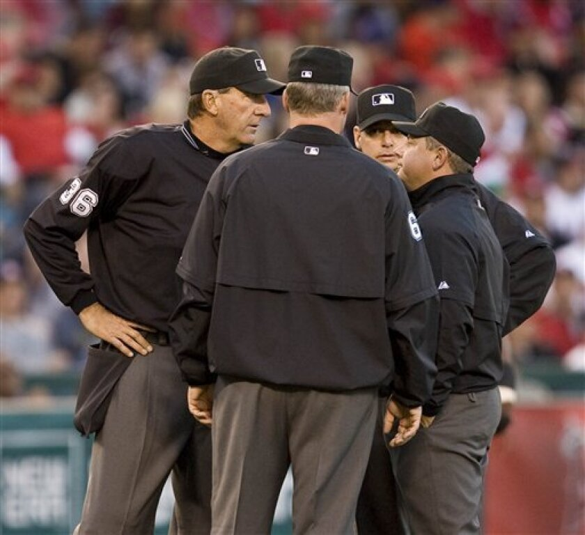 FILE - In this April 25, 2009, file photo, MLB umpires, from left, Tim McClelland , Ted Barrett, Andy Fletcher, and Greg Gibson, confer before viewing video of fan interference in the outfield after a hit by Los Angeles Angels' Gary Matthews Jr. in the third inning of a baseball game against the Seattle Mariners in Anaheim, Calif. Spurred by a blown call that cost Minnesota Twins' Armando Galarraga a perfect game on Wednesday, June 2, 2010, commissioner Bud Selig said he would look at the big picture: the possibility of expanded the use of video reviews. (AP Photo/Mark Avery,File)