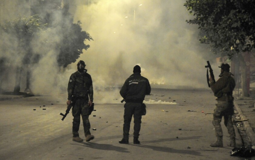 Three police officers stand on a smoke-shrouded street.