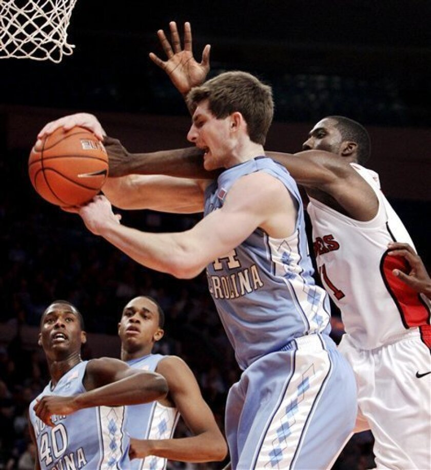 Rutgers guard Dane Miller (11) fouls North Carolina forward Tyler Zeller (44) in the second half of North Carolina's 78-55 victory over Rutgers in their NCAA college basketball game at Madison Square Garden in New York, Tuesday, Dec. 28, 2010.  At lower left, Carolina's Harrison Barnes, (40), and g