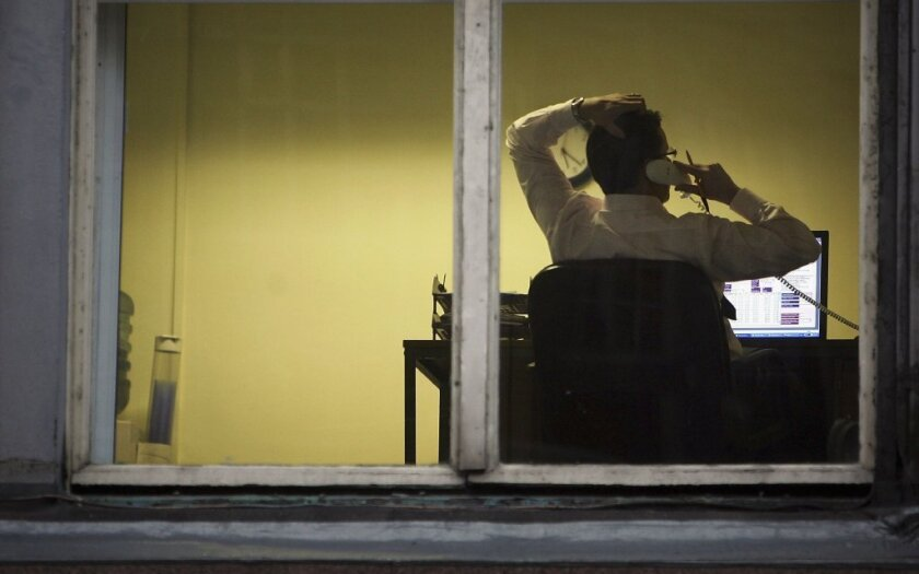 A man talks on the phone while working on a computer