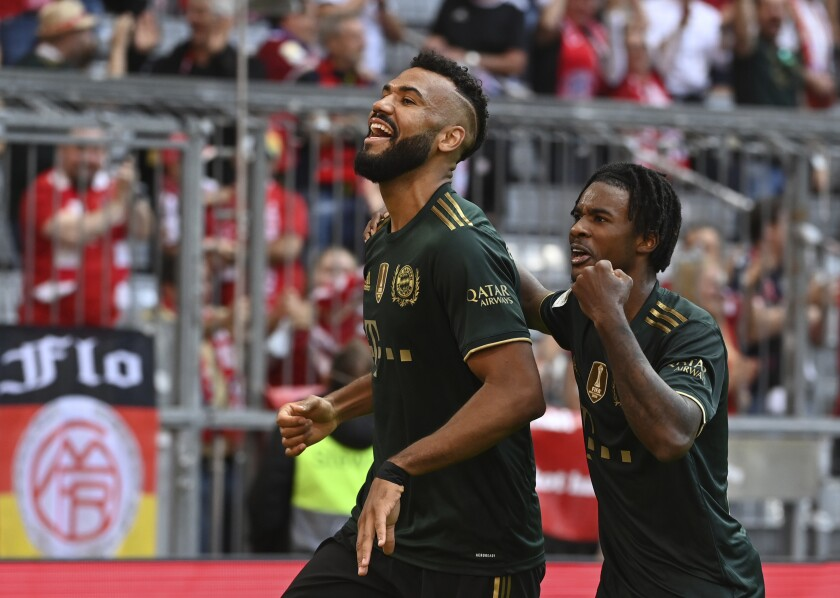 Munich's Eric Maxim Choupo-Moting, left, celebrates with Omar Richards after scoring his side's seventh goal during a German Bundesliga soccer match between Bayern Munich and VfL Bochum in Munich, Germany, Saturday, Sept.18, 2021. (Sven Hoppe/dpa via AP)