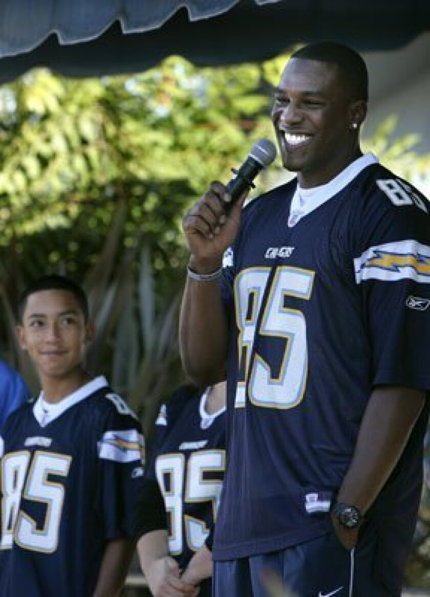 """Chargers tight end Antonio Gates talks with Hilltop Middle School students at an assembly Tuesday morning. Eighth grade student Cruz Jaime, left, won the """"Take an NFL Player to School"""" sweepstakes for the school. Howard Lipin / Union-Tribune"""