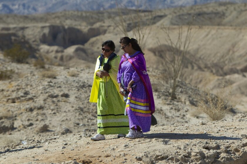 Yolanda Polk (left) and her sister, Lucia Polk (right), walk towards a hilltop to take part in the spirit wheel ceremony.
