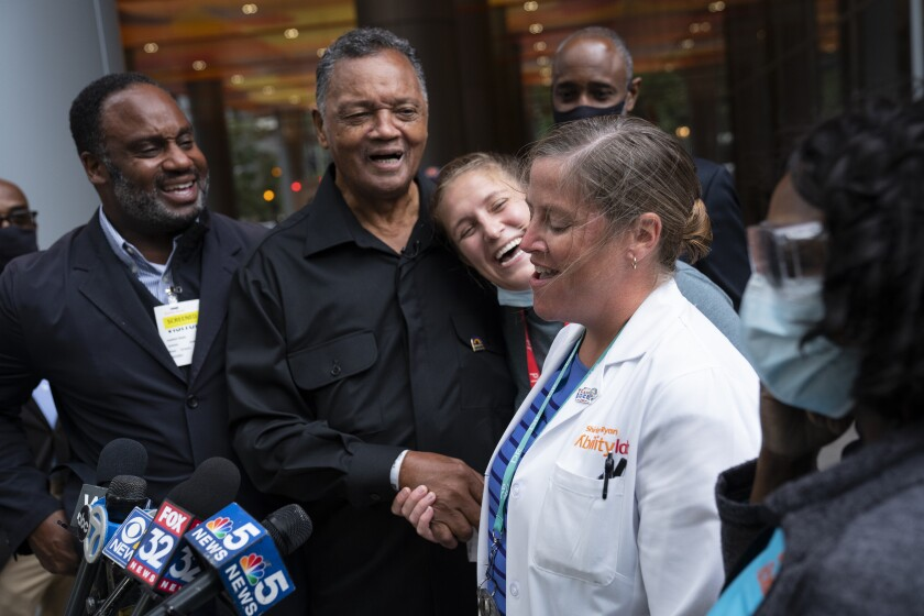 The Rev. Jesse Jackson jokes with his doctor, Dr. Leslie Rydberg, right, and physical therapist Talia Shapiro, center, as he is released from therapy at the Shirley Ryan AbilityLab after recovering from COVID-19, Wednesday, Sept. 22, 2021. (E. Jason Wambsgans/Chicago Tribune via AP)