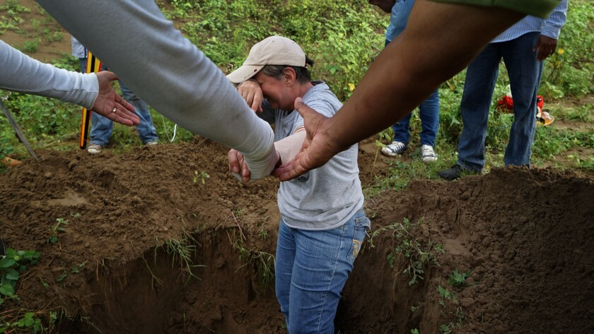 Rosalia Castro, 61, whose son disappeared in 2011, is overcome with emotion while helping to excavate a clandestine grave.