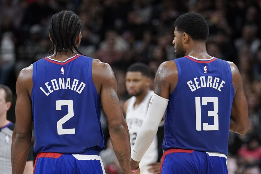 Clippers stars Kawhi Leonard and Paul George stand on the court together.