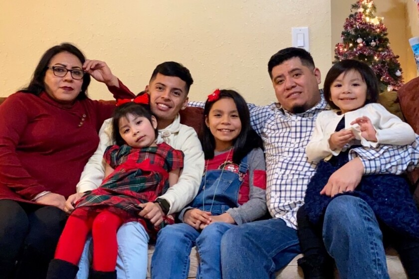 Maria Reyna Flores, left, and Juan Martinez, with their children