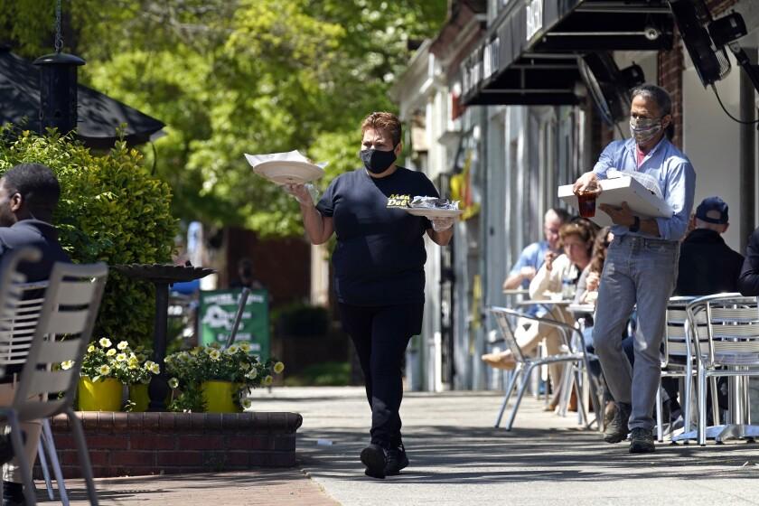 Une empleada de restaurante Mediterranean Deli lleva platillos a los comensales en el área de terraza