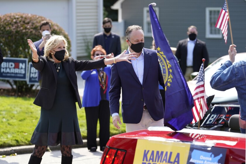 Jill Biden, left, wife of Democratic presidential candidate former vice president Joe Biden, and Doug Emhoff, center, husband of Democratic vice presidential candidate Sen. Kamala Harris, D-Calif., greet supporters in passing cars during a campaign stop, Wednesday, Sept. 16, 2020, in Manchester, N.H. (AP Photo/Steven Senne)