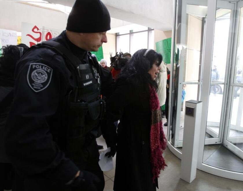 Fotografía donde se observa a un policía mientras de tiene a una mujer sin documentos. EFE/Kamil Krzaczynski/Archivo