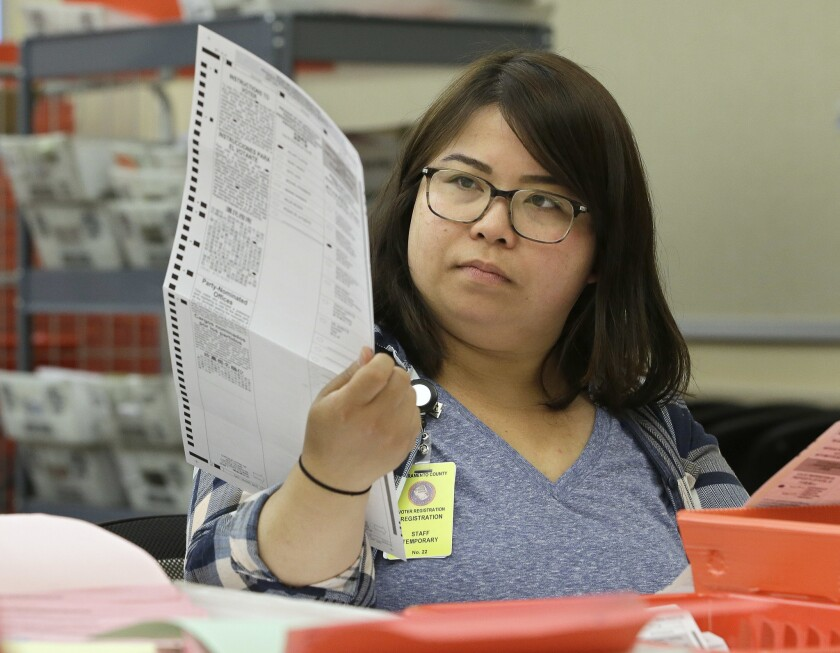 San Li, a temporary worker at the Sacramento County Registrar of Voters office, inspects a mail-in ballot before it is counted, Friday, June 10, 2016, in Sacramento, Calif.