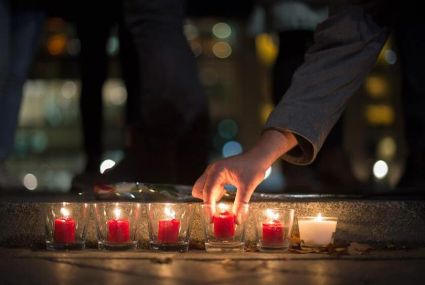 People light candles in tribute to the victims of the Paris attacks, outside the French embassy in Berlin, Germany, 13 November 2015. Dozens of people have been killed in a series of attacks in Paris on 13 November.