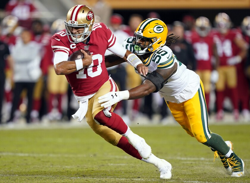 San Francisco quarterback Jimmy Garoppolo is chased by Green Bay linebacker Za'Darius Smith during the 49ers' 37-8 victory Sunday night.