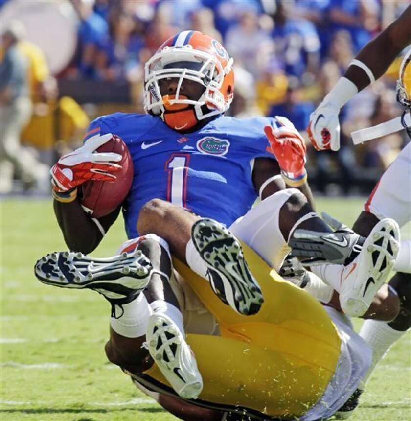Florida running back Chris Rainey (1) is wrapped up by LSU cornerback Tyrann Mathieu (7) in the first half of an NCAA college football game in Baton Rouge, La., Saturday, Oct. 8, 2011. (AP Photo/Bill Haber)