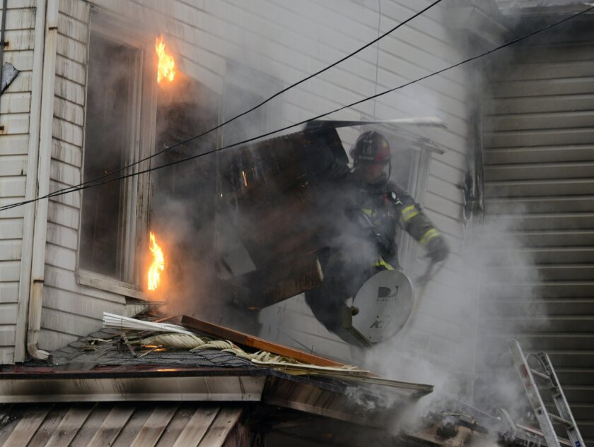 A City of Pittsburgh firefighter pulls back siding on the second floor to expose fire at the scene of a fatal fire at a boarding house in Pittsburgh, Wednesday, Feb. 17, 2016. Fire Chief Darryl Jones said heavy flames were visible when crews arrived, and the fire was so intense that it set off an a