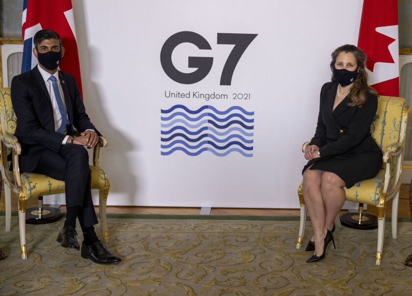 Britain's Chancellor of the Exchequer Rishi Sunak, left, sits with Canada's Finance Minister Chrystia Freeland, ahead of the G7 finance ministers meeting at Lancaster House in London, Friday June 4, 2021. (Steve Reigate/Pool via AP)