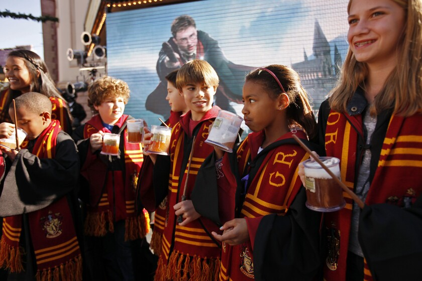 Sarah Miller, 11, Imani Wiley, 9, and Colby Rogers, 12, right to left, taste Butterbeer, a popular beverage from the Harry Potter books and movies, during a press conference in 2011 to announce the new Harry Potter attraction at Universal Studios Hollywood. The park launched an interactive map Tuesday to give fans a peek at the attraction, set to open in the spring of 2016.