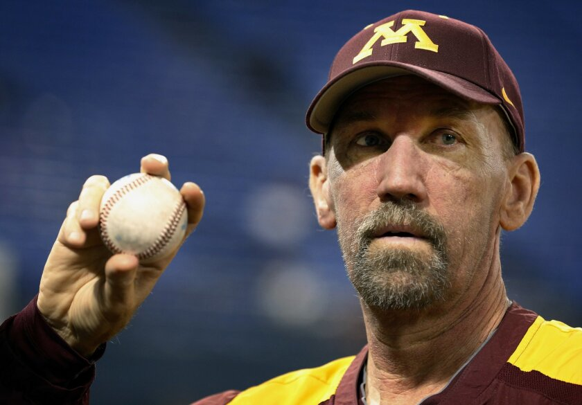 In this Feb. 27, 2013 photo, Minnesota Gophers pitching coach Todd Oakes holds a ball before an NCAA college baseball game in Minneapolis. The top-seeded Gophers have much more to keep them going this week in postseason play with somber thoughts of leukemia-stricken pitching coach Todd Oakes, who h