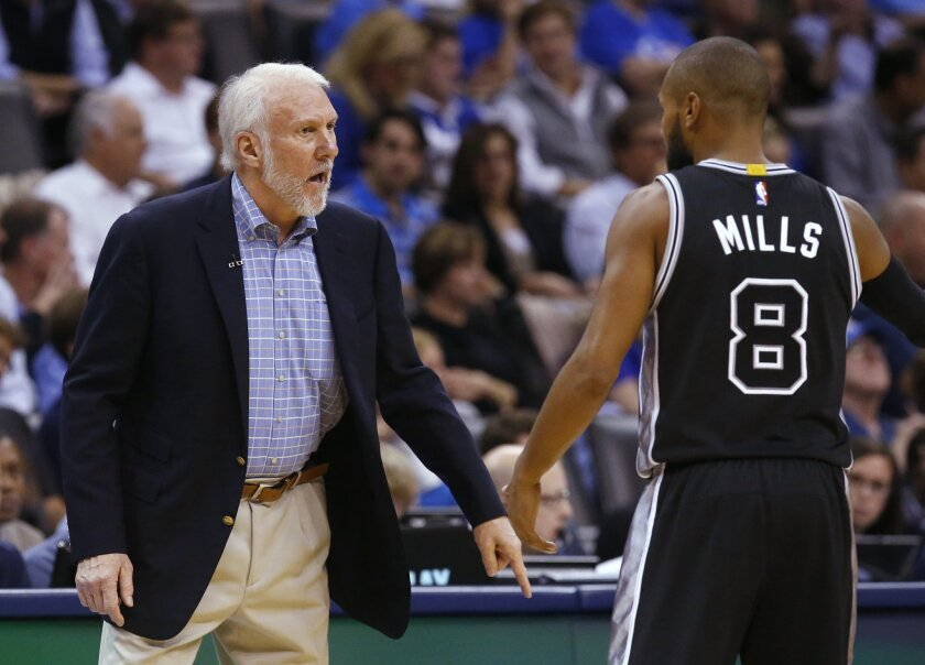 San Antonio Spurs coach Gregg Popovich talks with guard Patty Mills (8) during the second quarter of an NBA basketball game against the Oklahoma City Thunder in Oklahoma City, Wednesday, Oct. 28, 2015. Oklahoma City won 112-106. (AP Photo/Sue Ogrocki)